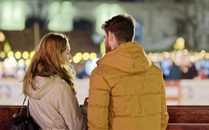 Eine Frau schaut in die Ferne und hört nicht zu, während ein Mann mit ihr spricht