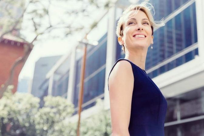An einem sonnigen Mittag lächelt eine ausgeruht und entspannt wirkende Geschäftsfrau, während sie sich beim Laufen nach hinten umdreht.