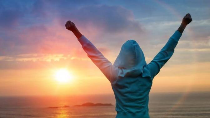 Eine Frau steht in typischer Siegerpose mit erhobenen Armen auf einem Berg und blickt auf die untergehende Sonne über dem Meer vor ihr.