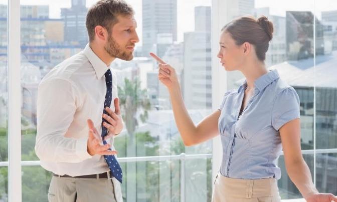 Zwei Menschen streiten in einer Büroumgebung, die eine Person beschuldigt ganz offensichtlich die andere.