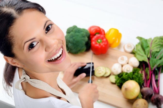 Eine Frau schneidet Obst und Gemüse und lächelt