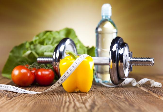 Eine Hantel liegt zwischen Obst und Gemüse