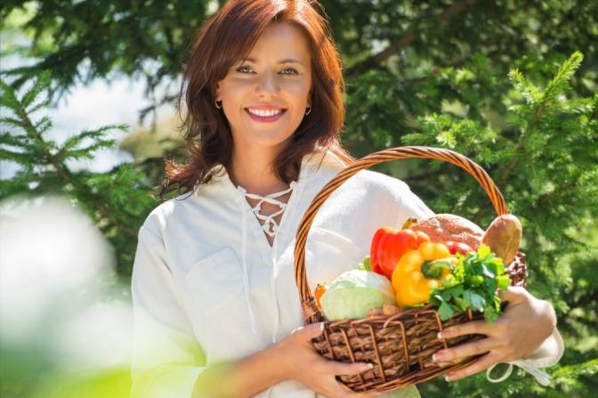 Eine Frau hält einen Korb mit Gemüse