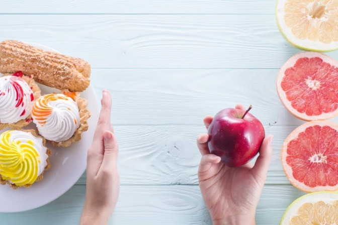 Hand weist Süßigkeiten ab und greift zu Zitrusfrüchten und Obst