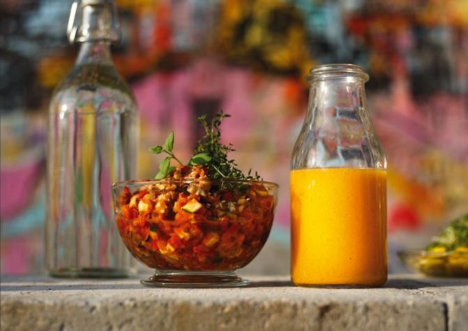 Eine Flasche mit Obstsmoothie steht neben einer Schüssel mit Obstsalat