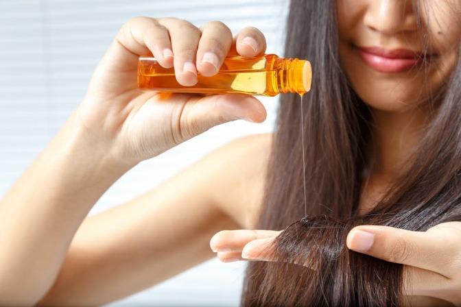 Frau gibt Öl auf Haare