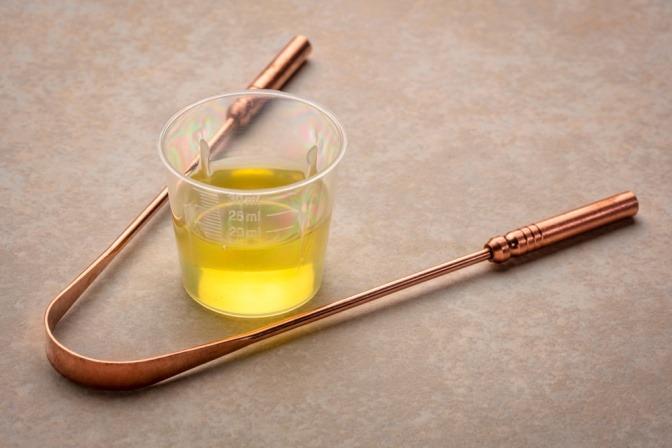 Zungenschaber und Becher mit Öl