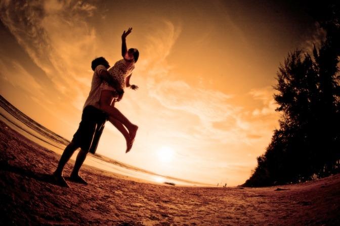 Ein Mann hebt eine Frau, frei von Bewertungen, in die Höhe