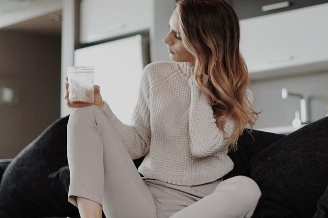 Eine Frau ohne Stress sitzt auf der Couch und hält die Ohren