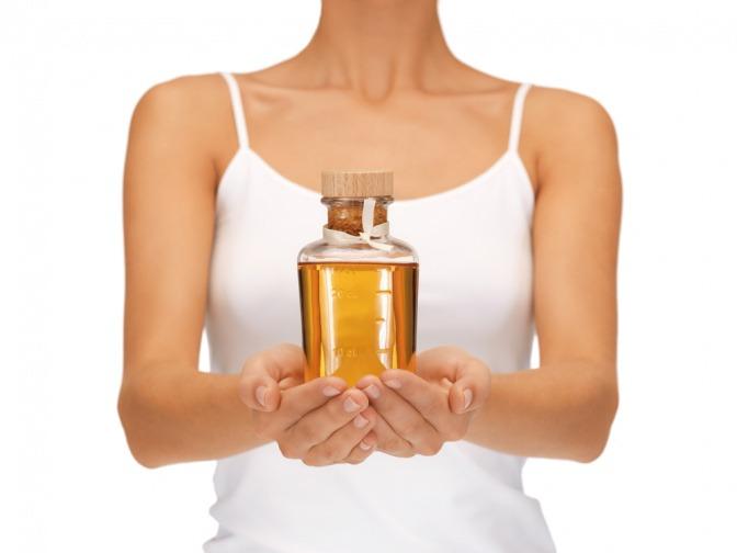 Frau mit einer kleinen Kanne Olivenöl für ihre Haut in der Hand