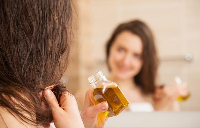 Eine Frau gibt Olivenöl auf die Haare