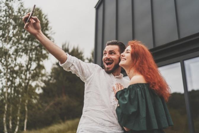 Bärtiger Mann und rothaarige Frau, die sich im Internet kennengelernt und verliebt haben, machen ein Selfie.