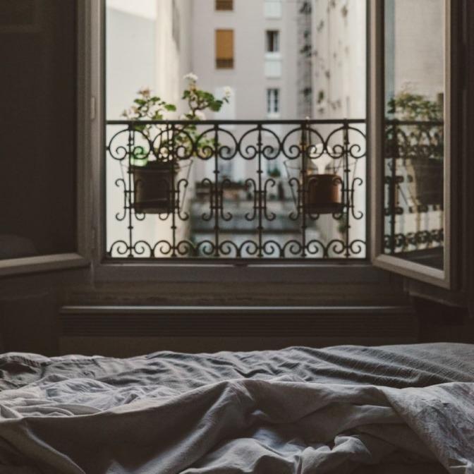 In einem Schlafzimmer sind die Fenster offen
