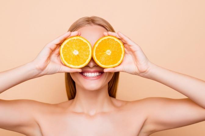 Frau hält Zitronenscheiben vor ihre Augen.