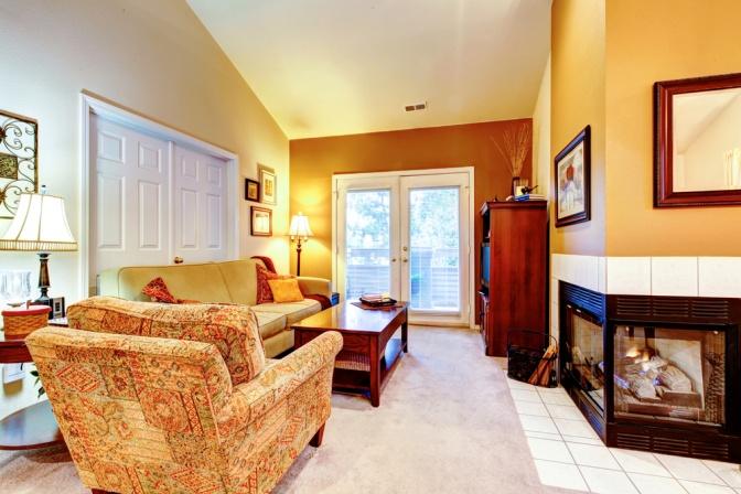 In einem rot und orange eingerichteten Zimmer gibt es einen Kamin