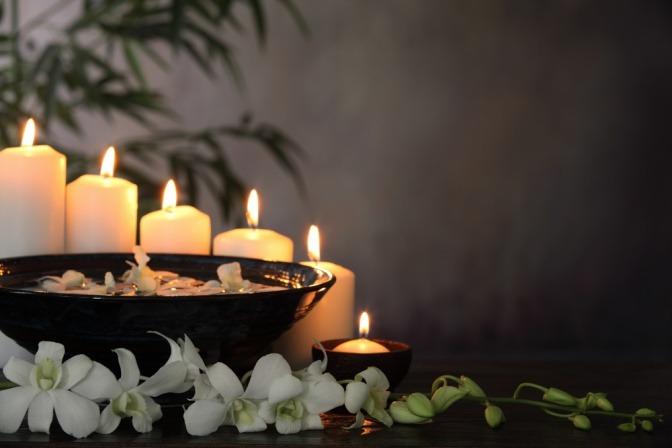 Eine weiße Blume steht in einer grauen Vase
