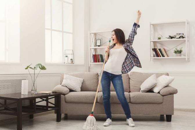 Eine fröhliche junge Frau nach dem Aufräumen in ihrer Wohnung.