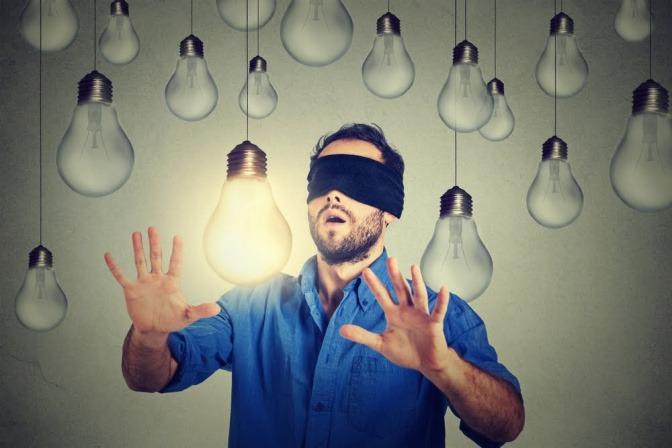 Ein Mann mit einer Augenbinde ist in einem Raum voller Glühbirnen, die von der Decke hängen. Eine der Birnen leuchtet.