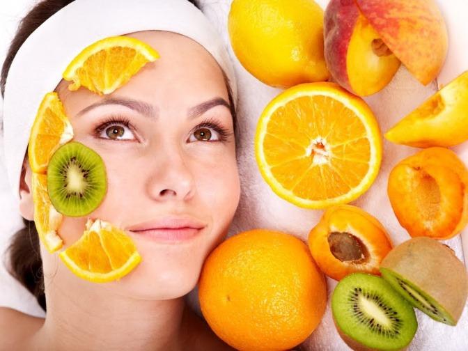 Eine Frau wendet organische Kosmetik in ihrer Urform an. Sie hat sich einige Scheiben von diversen Zitrusfrüchten auf ihr Gesicht gelegt.