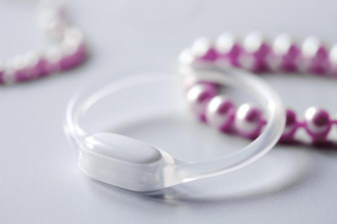 Ein OvulaRing liegt neben einer Perlenkette