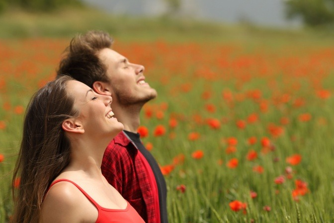 Ein Paar befindet sich auf einer Mohnblumenwiese und atmet tief durch