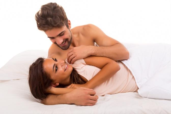 Eine Mann und eine Frau im Bett sehen sich glücklich an