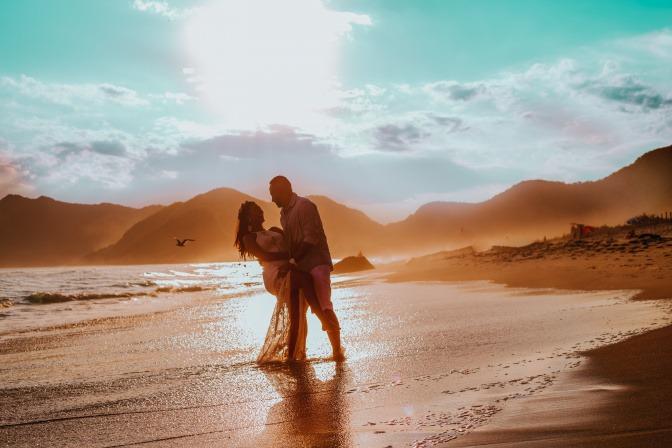 Ein Paar macht einen Spaziergang am Strand und springt dabei händchenhaltend über Stellen mit flachem Wasser.