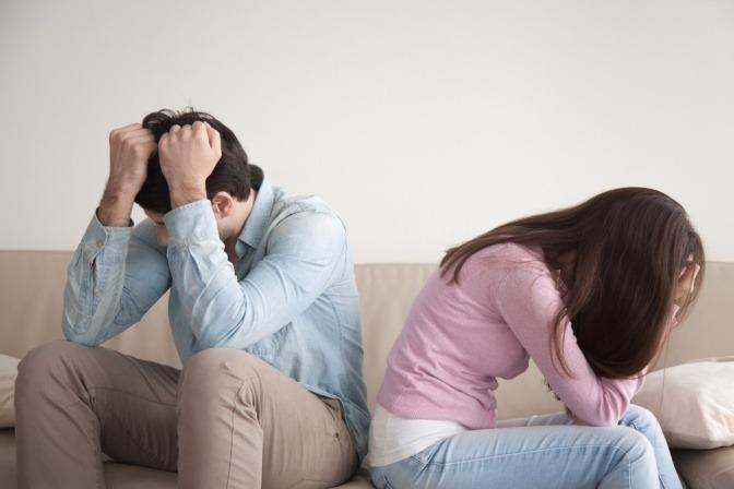 Ein unglückliches Paar sitzt auf einer Couch