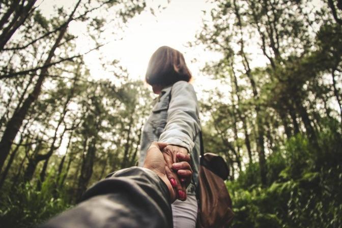 Ein Pärchen befindet sich im Wald und hält sich an den Händen