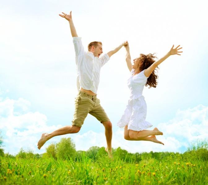 Ein Pärchen springt voller Lebensfreude in die Luft