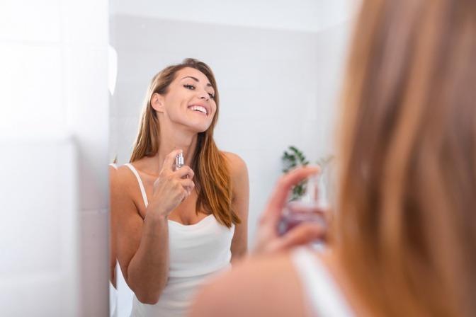 Eine Frau trägt mit Selbstvertrauen Parfum auf
