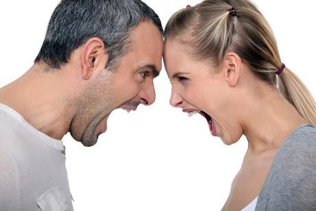 Ein Paar steht sich Kopf an Kopf gegenüber und schreit sich an.