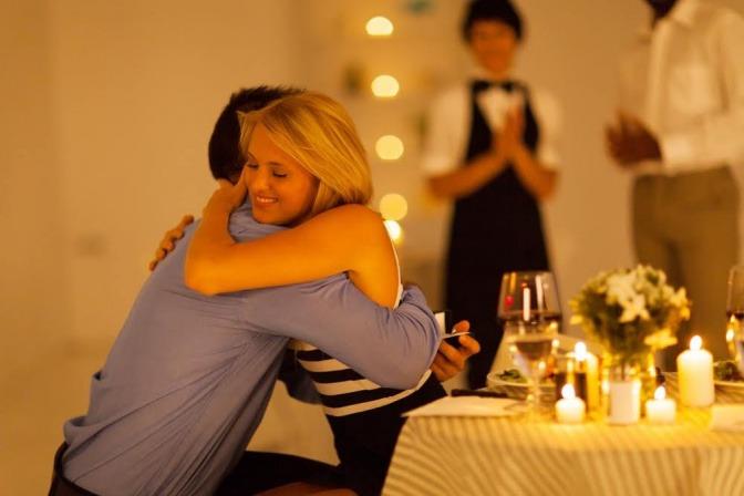 Ein Paar umarmt sich bei einem romantischen Dinner in einem Restaurant.