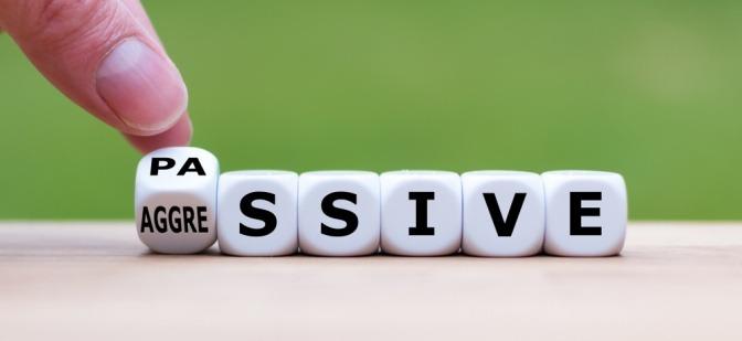 Eine Hand dreht einen Würfel um und verändert das Wort passiv in aggressiv