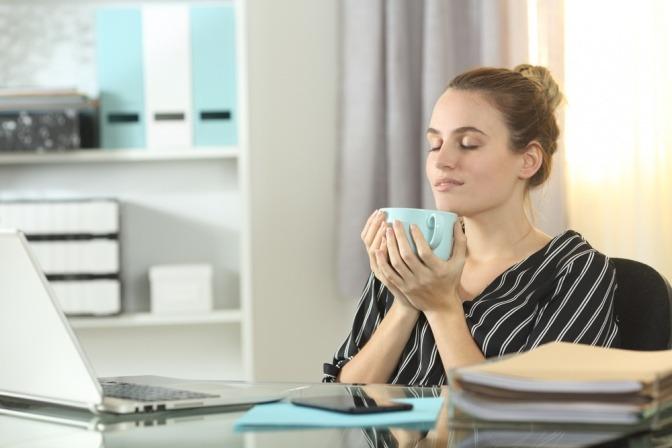 Frau im Homeoffice trinkt entspannt Kaffee