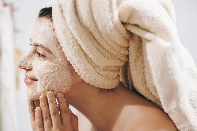 Frau mit Peeling im Gesicht gegen Hautunreinheiten