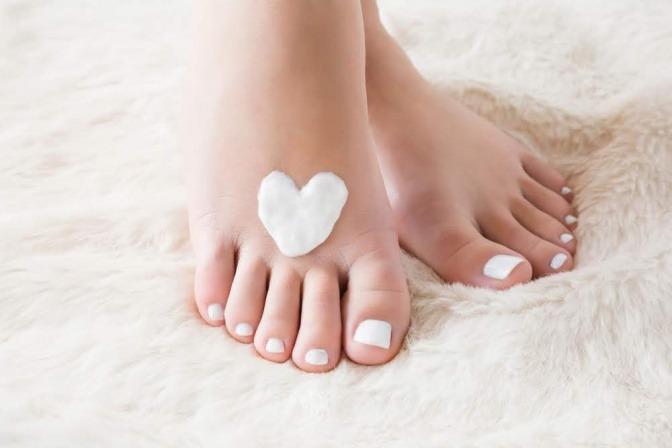 Wir sehen die Füße einer aufrecht stehenden Frau. Auf dem rechten Fuß hat sie ein Herz aus pflegender Fußcreme aufgetragen.