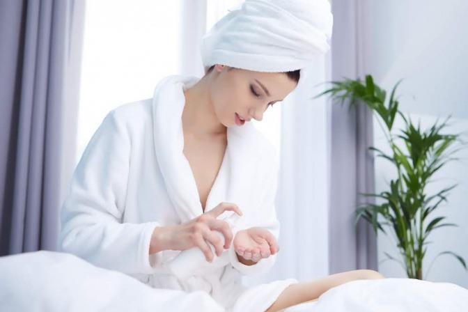 Eine junge Frau mit langen blonden Haaren hat ein Handtuch um ihren Körper gewickelt
