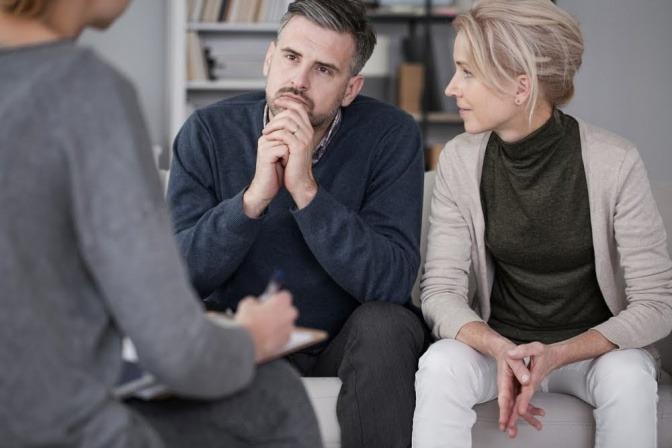 Ein Mann sitzt während eines Paarcoachings auf einem Sofa und nimmt den Rat einer Beziehungsarchitektin entgegen.
