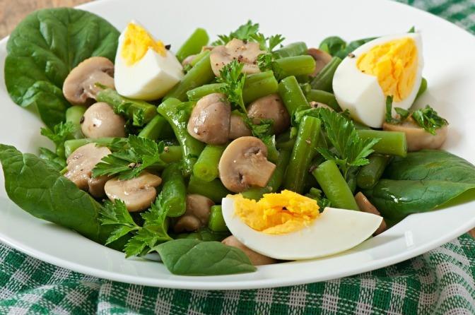 Pilze, Hülsenfrüchte und Eier liegen mit Salat auf einem Teller