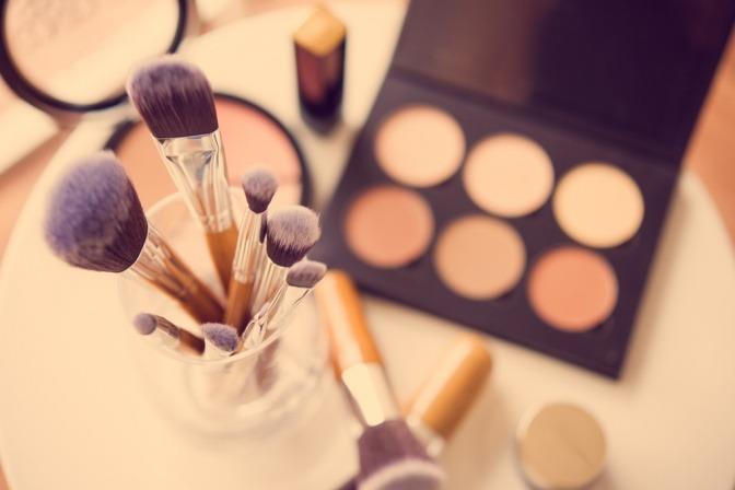 Mit Make-up-Pinseln trägt man Camouflage Make-up in verschiedenen Hauttönen auf
