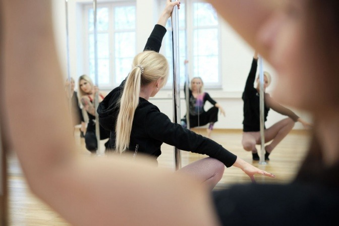 Frau macht Pole Dance