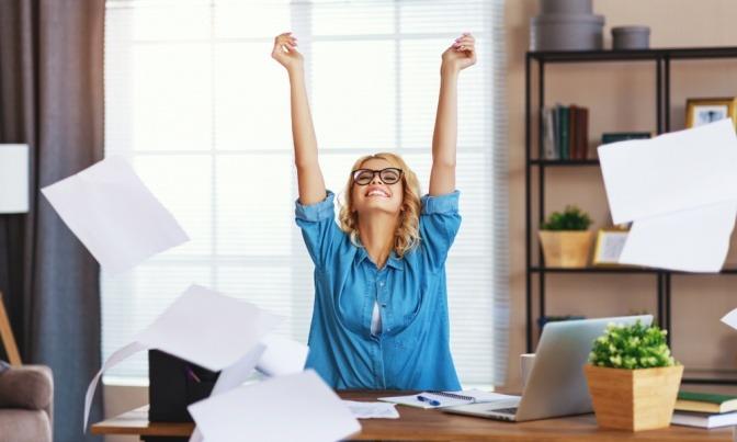 Eine junge, glückliche Geschäftsfrau arbeitet am Computer und wirft Papiere im Home Office umher.