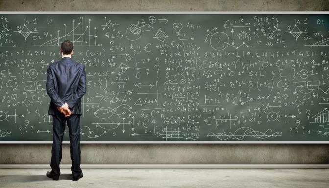 Ein Mann in einem Anzug steht vor einer großen Tafel, die vollgeschrieben ist mit komplizierten Formeln und Gleichungen.