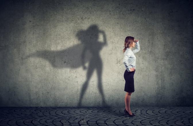 Eine Frau steht seitlich vor einer Wand und blickt in die Ferne, sie scheint etwas zu suchen. Ihr Schattenwurf an der Wand zeigt die Umrisse einer Superheldin.