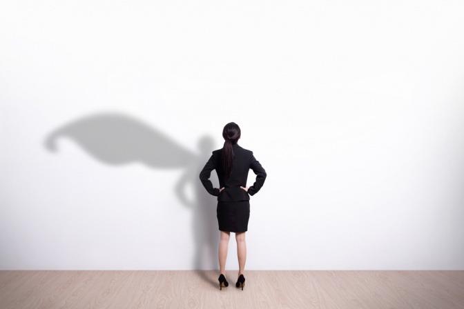 Eine Business-Frau steht vor einer weißen Wand, an der sich ihr Schatten in Form eines Superhelden abzeichnet