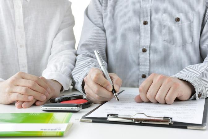 Ein Ehepaar sitzt nebeneinander, er schreibt eine Liste auf einem Klemmbrett.