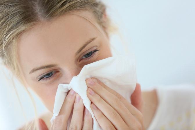 Frau mit Taschentuch vor dem Gesicht