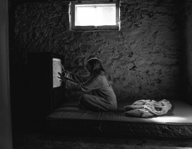 Eine Frau sitzt auf ihrem Bett und greift nach dem Fernseher vor ihr, auf dem jedoch nur Rauschen zu sehen ist.