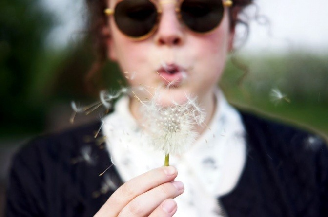 Eine Frau hält eine Pusteblume in ihren Händen